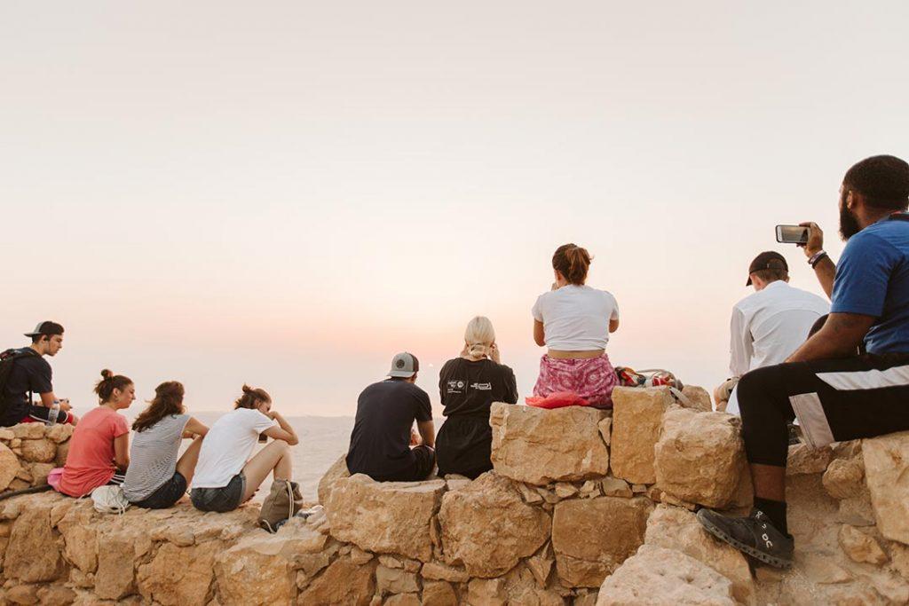 people watching the sunrise at masada