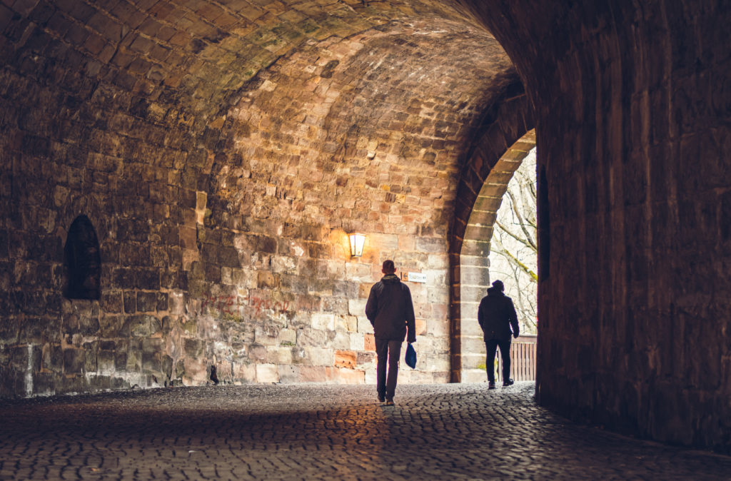 two men walking through a tunnel in the city