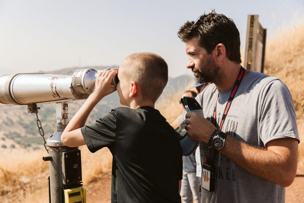 aaron shust and son looking through telescope